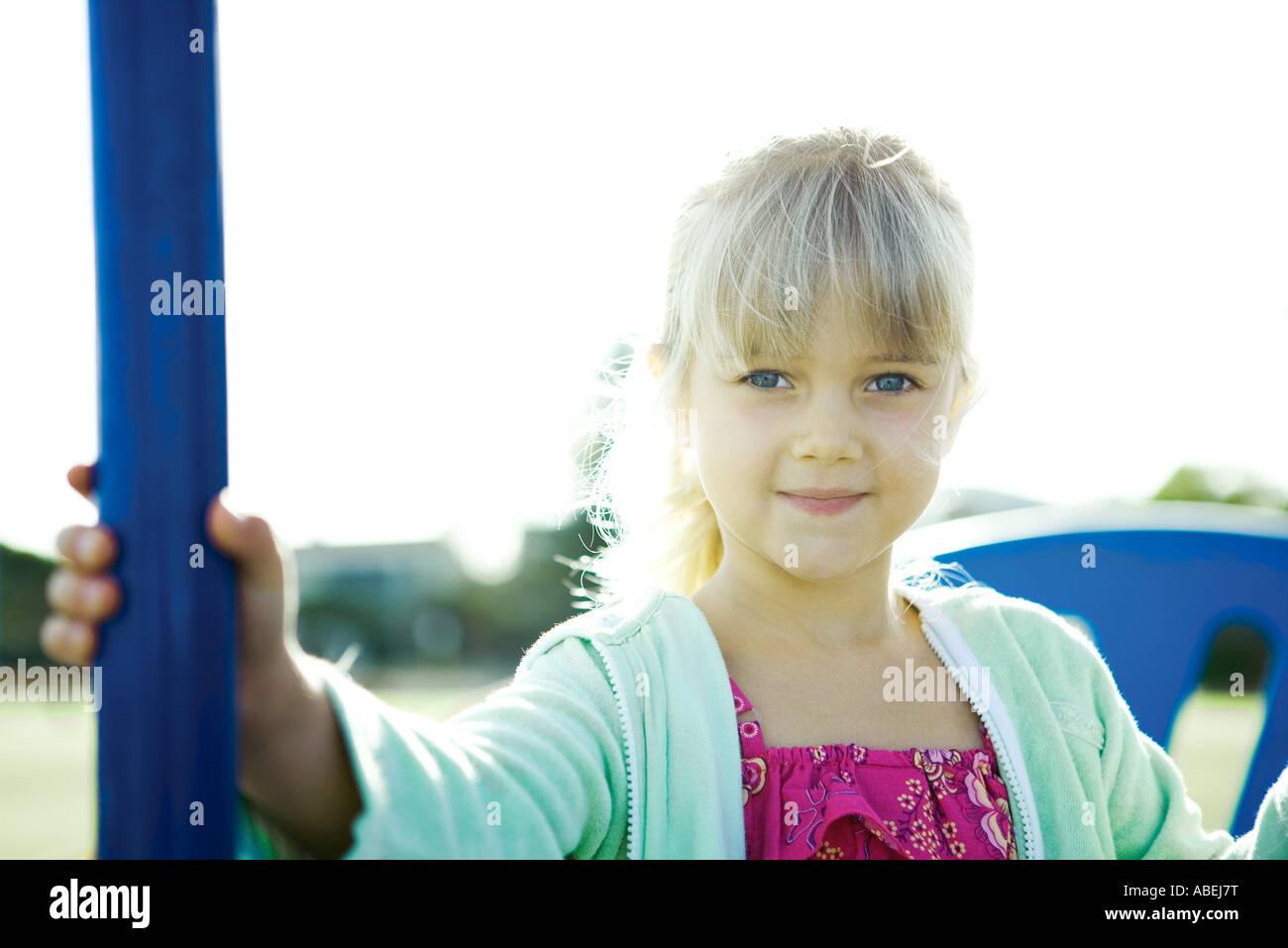 Girl on playground equipment, smiling at camera - Stock Image