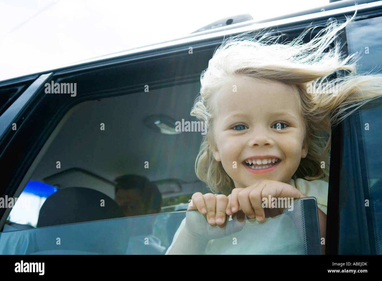 Little girl in car, looking out of window, smiling at camera, hair blowing in wind Stock Photo