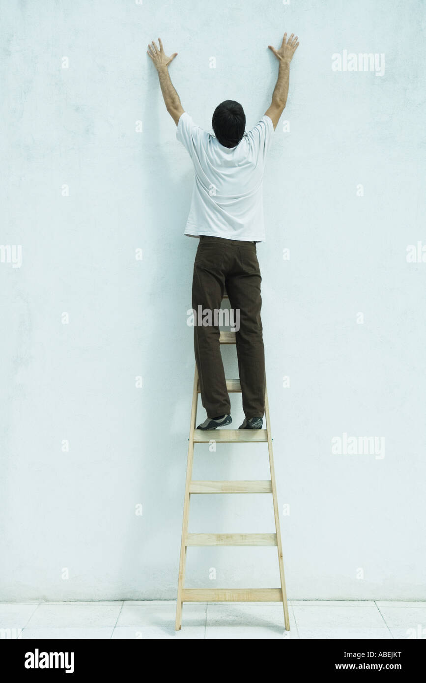 Man standing on ladder, reaching up along wall, full length Stock Photo