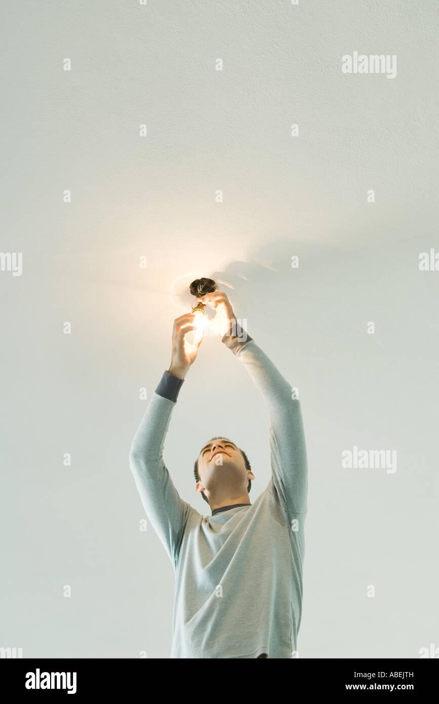 Man changing lightbulb - Stock Image