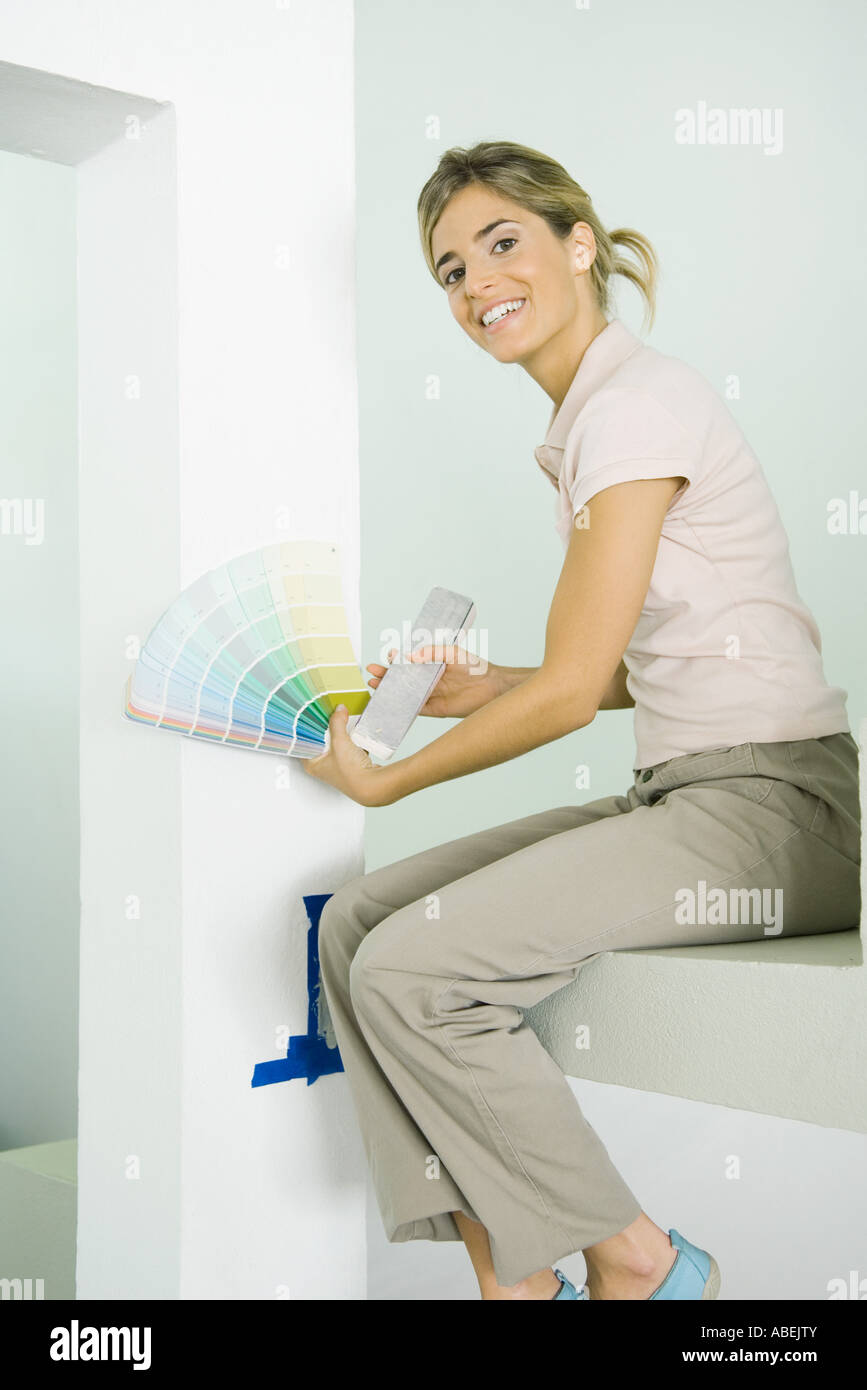 Woman holding up paint swatches - Stock Image