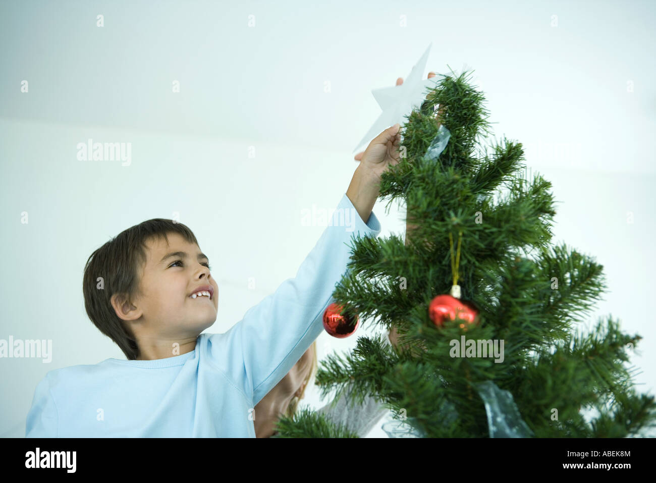A Star For Christmas.Boy Putting Star On Top Of Christmas Tree Stock Photo