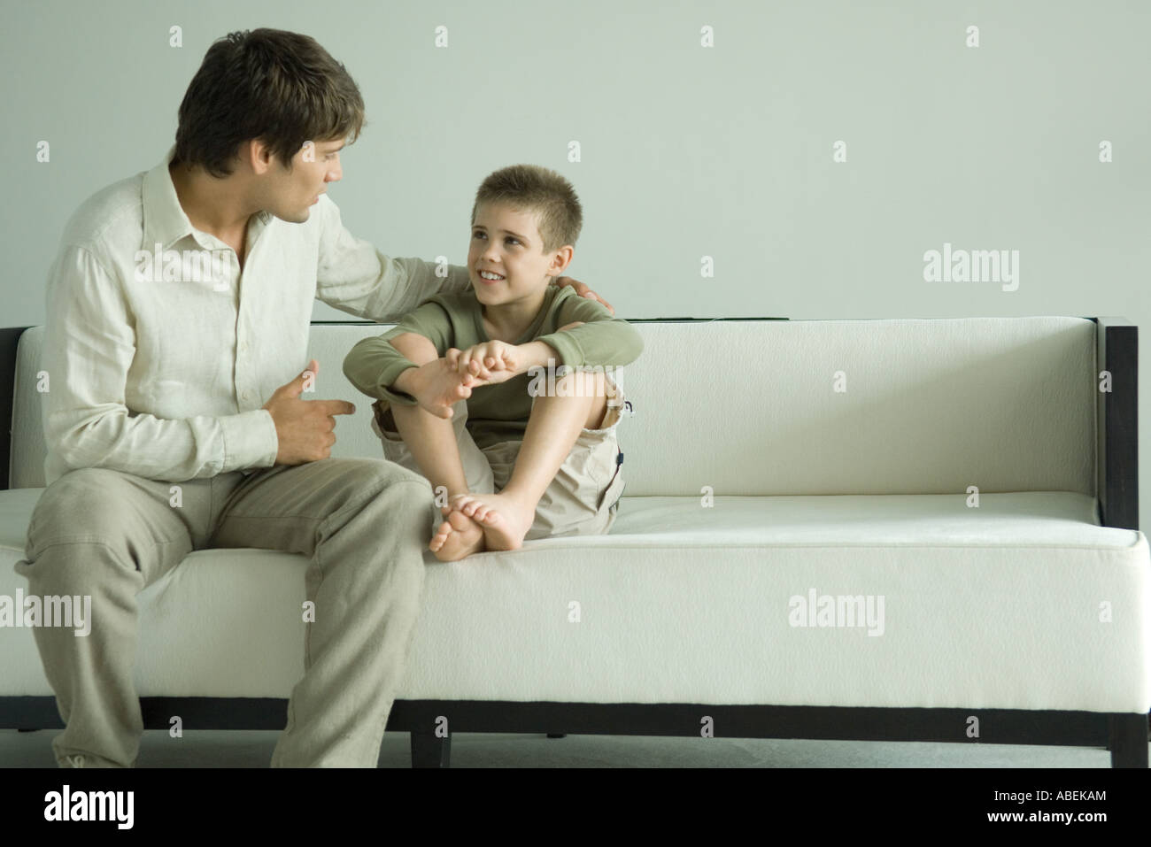 Father and son sitting on sofa, talking - Stock Image