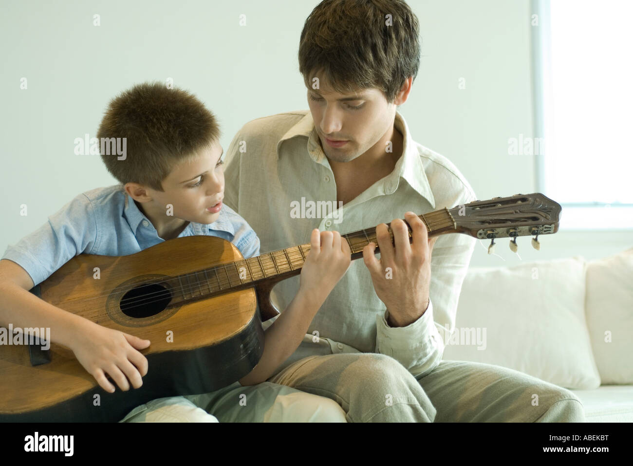 Father and son playing guitar together Stock Photo