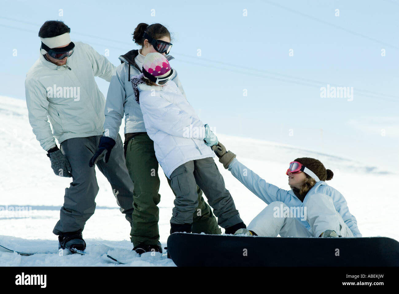 Girl sitting on ground, on snowboard, being pulled up by friends - Stock Image