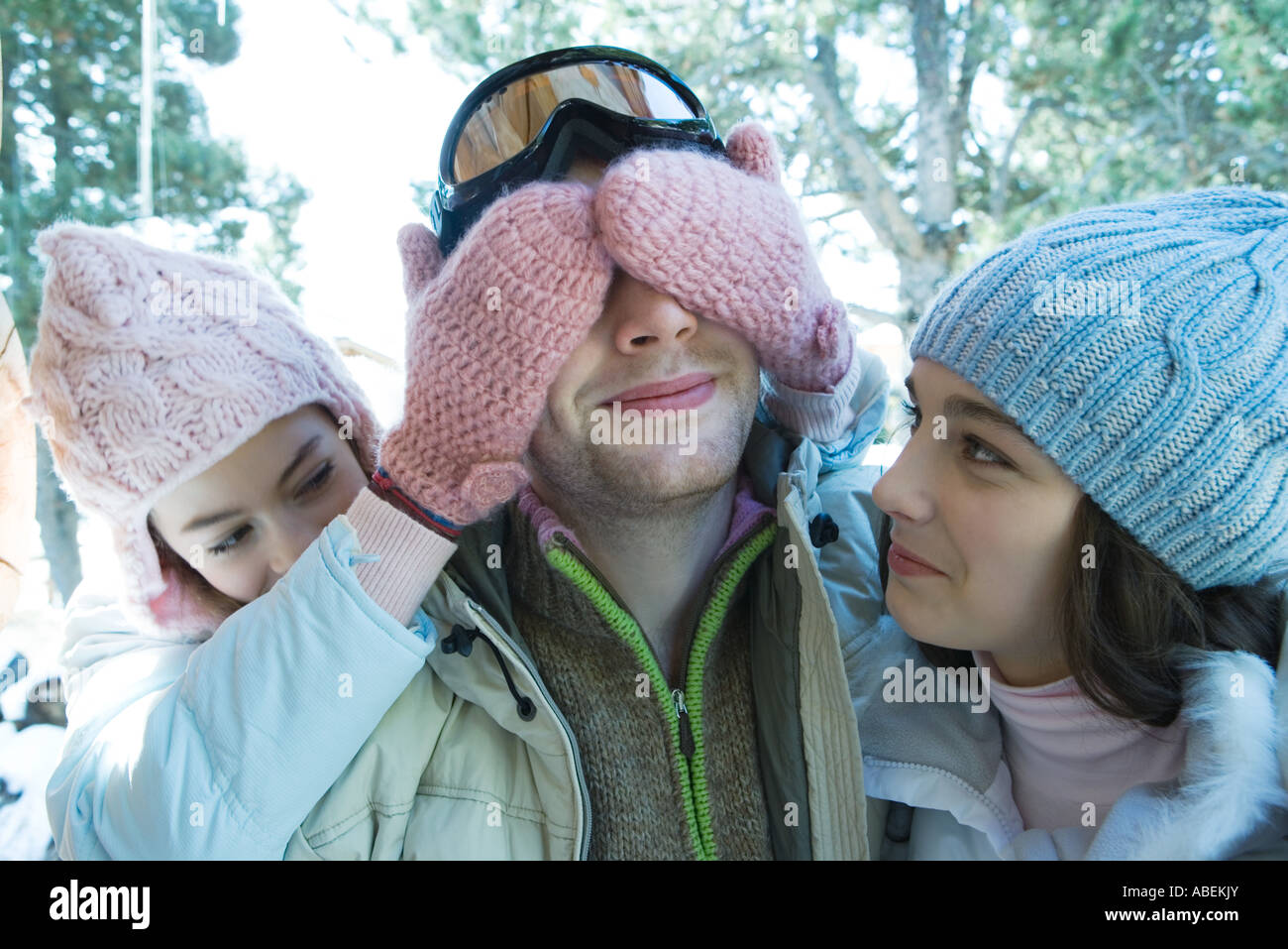 Teen girls with young man, one covering his eyes - Stock Image