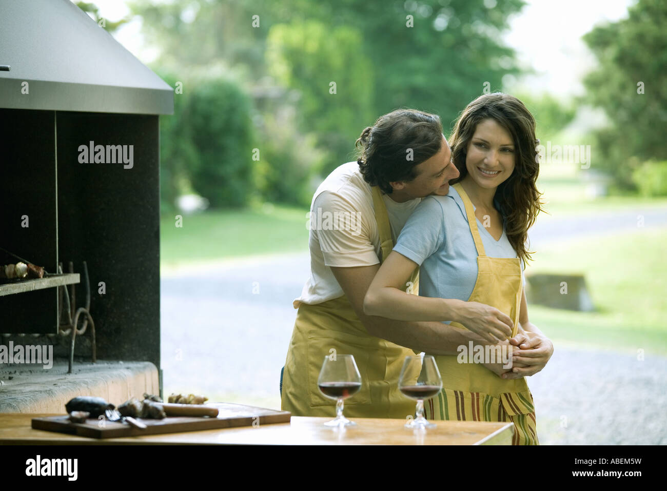 Couple standing near outside wood oven, man holding woman from behind, putting head on her shoulder - Stock Image