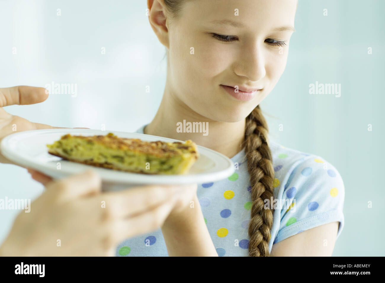 Girl making face at piece of quiche Stock Photo