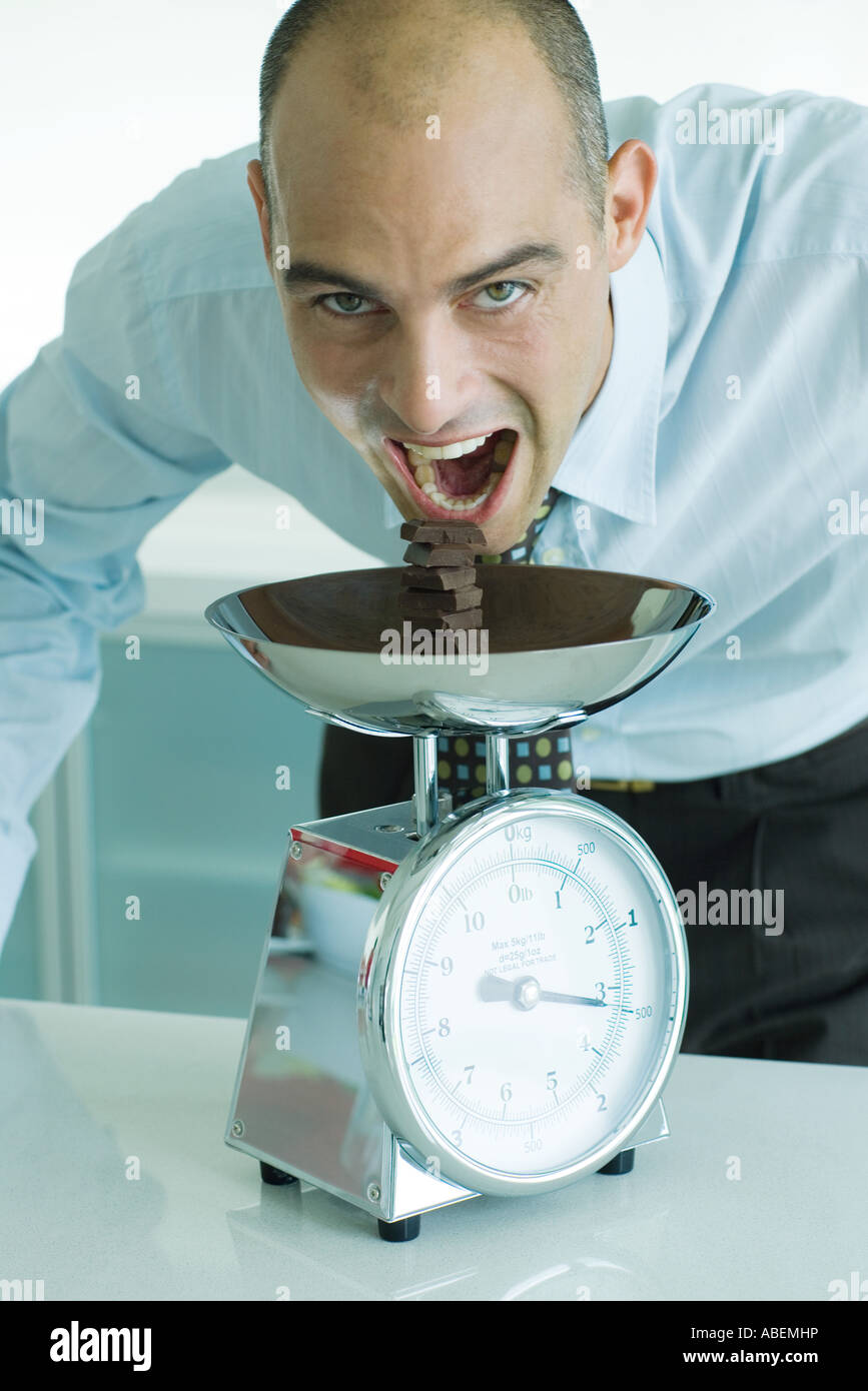 Man leaning toward stack of chocolate chunks on kitchen scale with mouth wide open - Stock Image