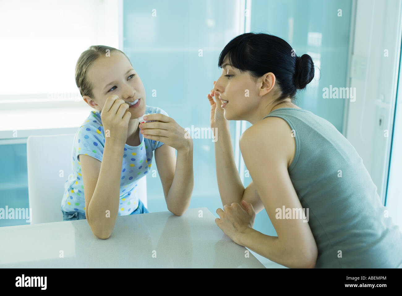 Girl eating ice cream dessert, woman leaning toward girl enviously - Stock Image