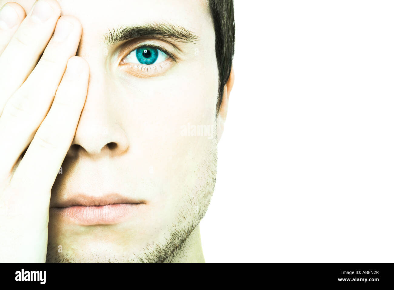 Young man covering one eye, looking at camera, extreme close-up - Stock Image