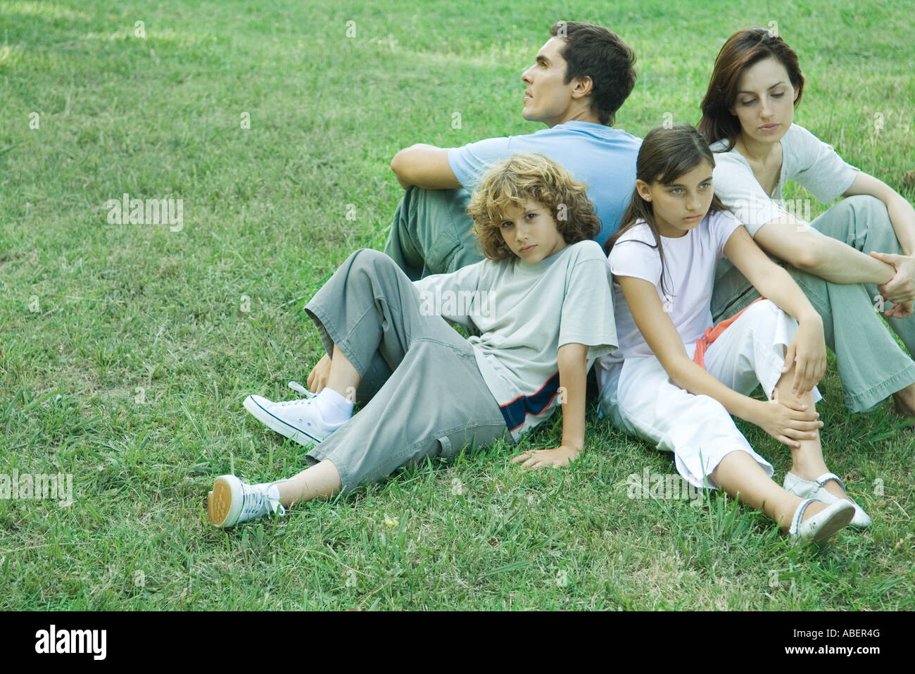 Family outdoors, sitting on grass back to back - Stock Image