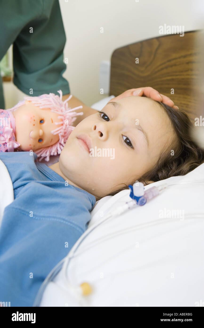 Girl lying in hospital bed - Stock Image
