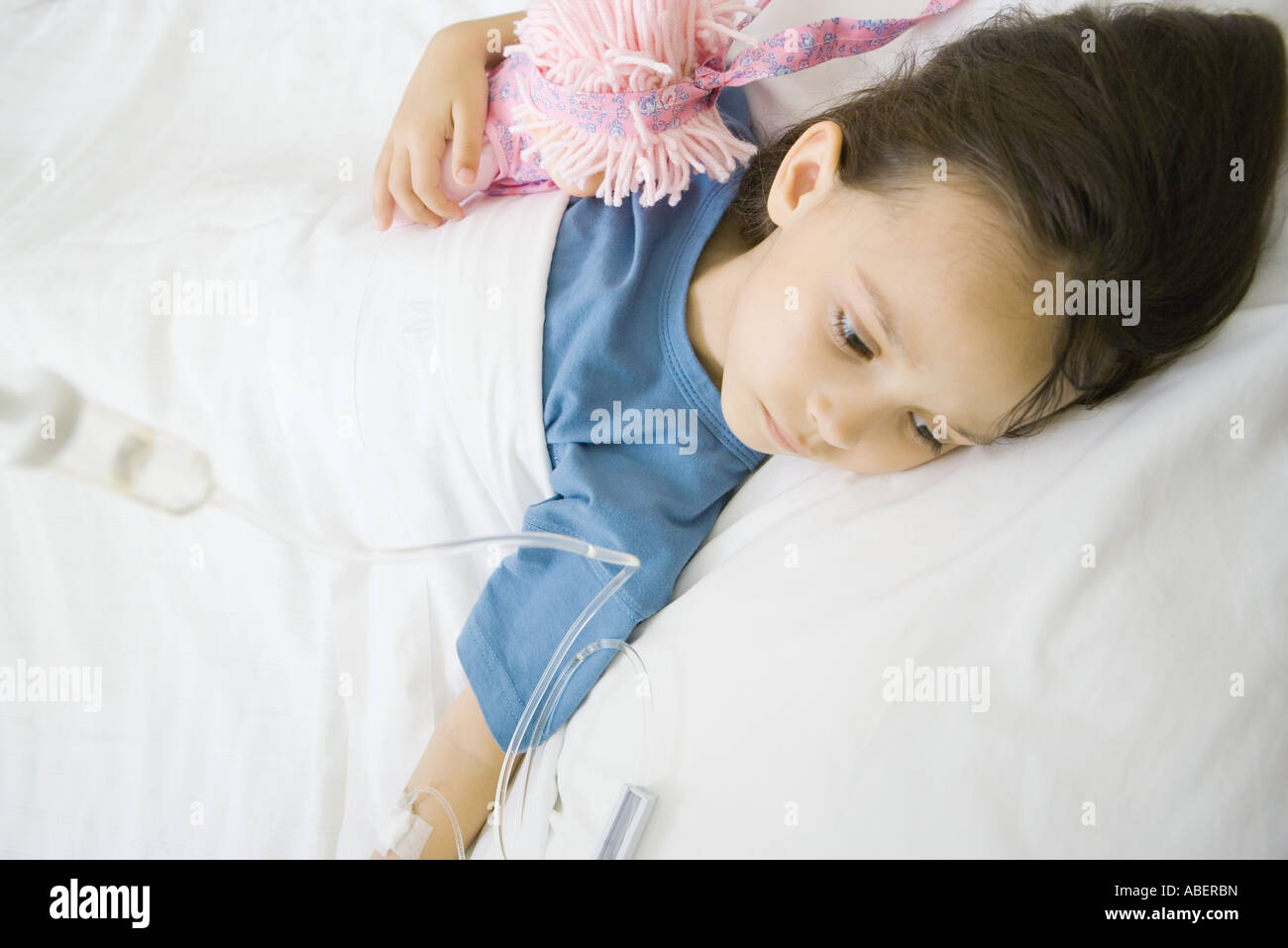 Girl lying in hospital bed - Stock Image