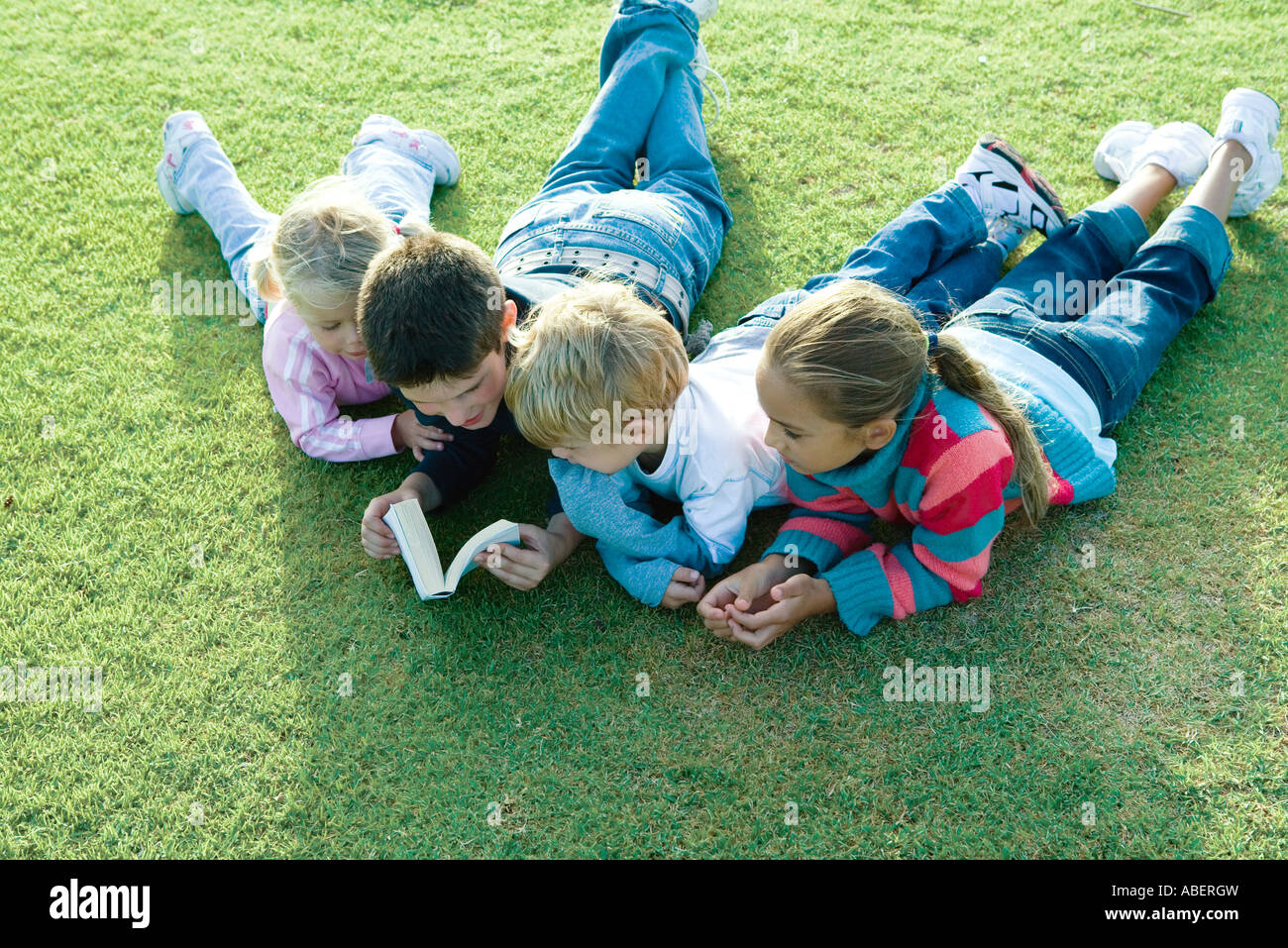 Children lying on grass together, reading - Stock Image