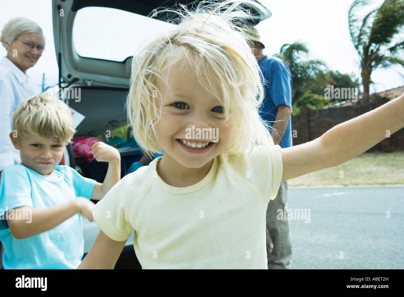 Family unloading trunk of car, focus on little girl in foreground Stock Photo
