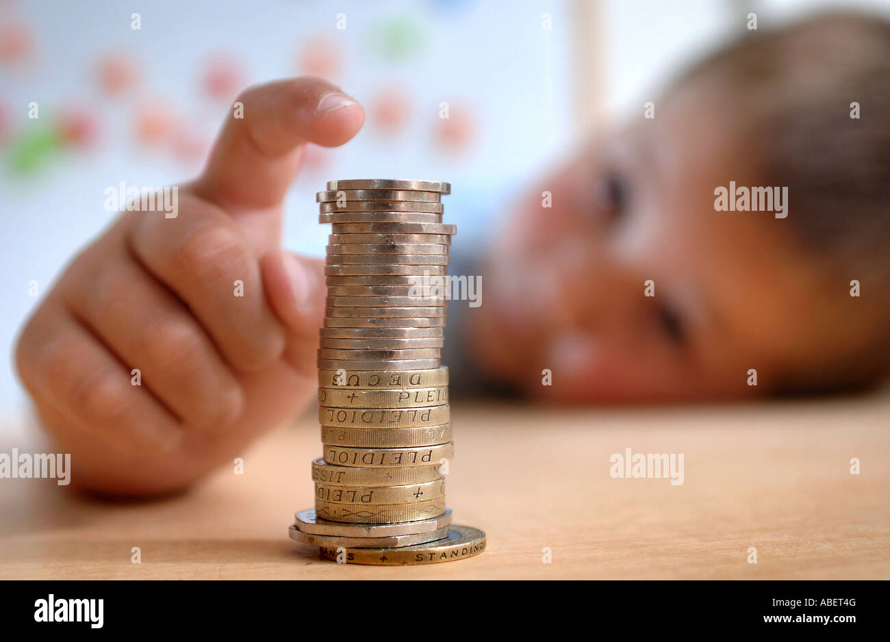 A young boy pictured with a stack of coins sat at a desk. - Stock Image