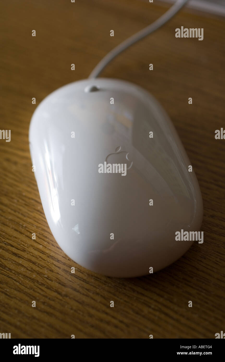 An Apple Mighty Mouse on a wooden desktop - Stock Image