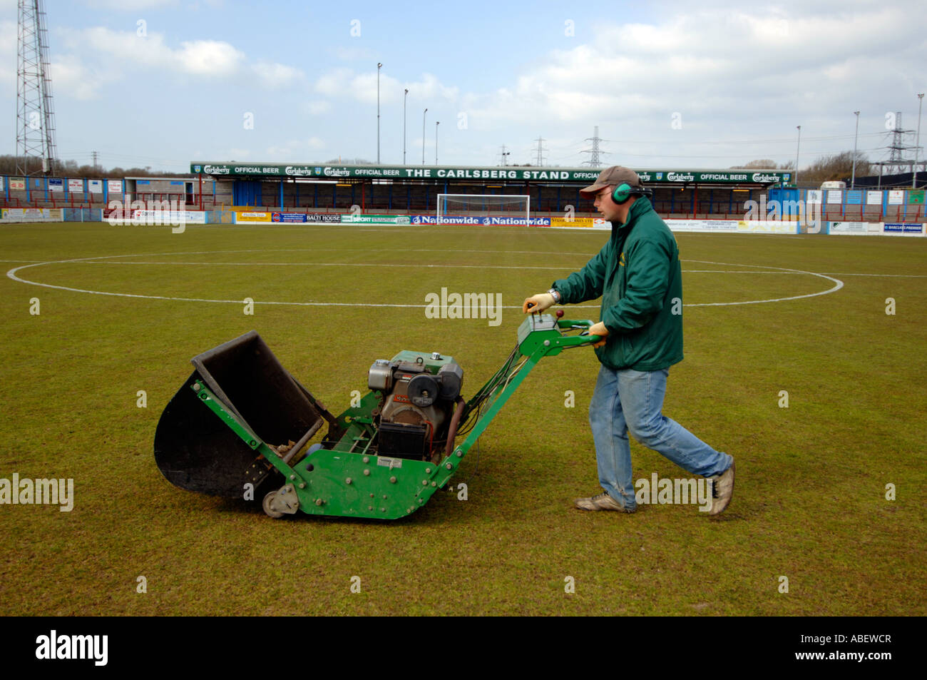 Groundsman mowing a football ground pitch, Britain UK - Stock Image