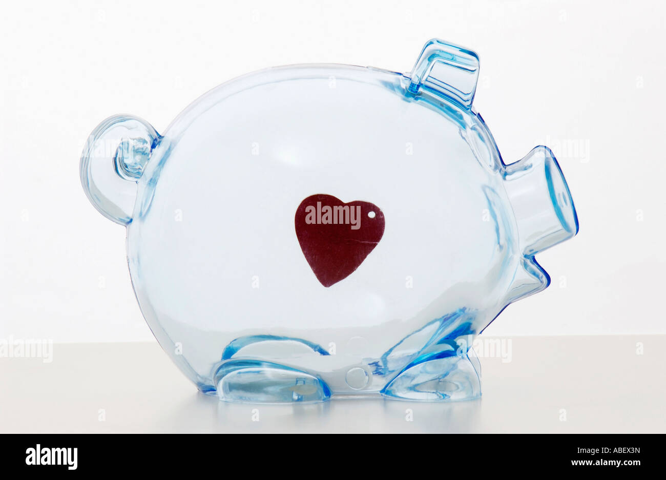 Suspended heart shape in piggy bank - Stock Image