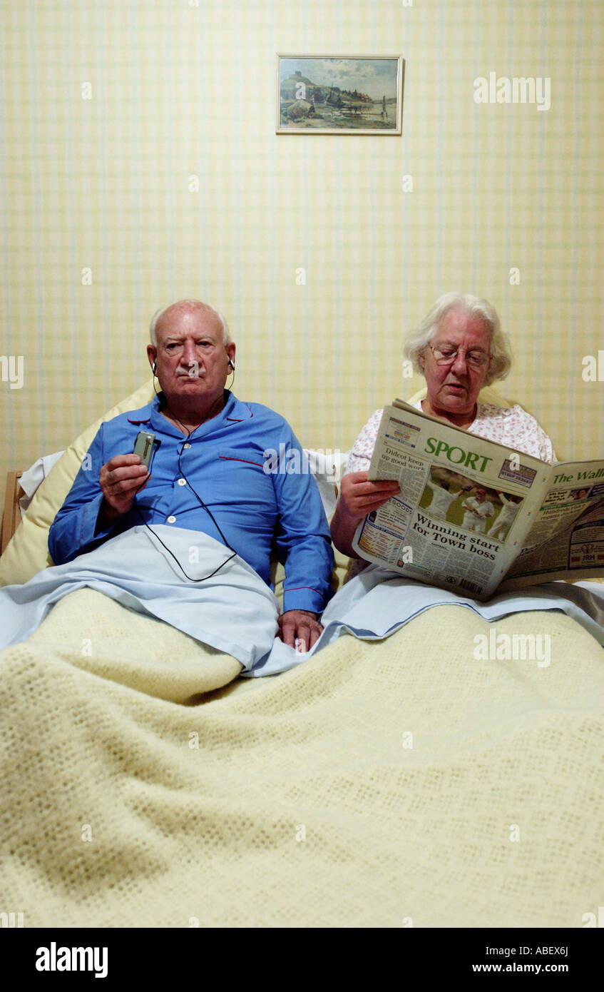 Senior couple in bed, woman reading newspaper - Stock Image