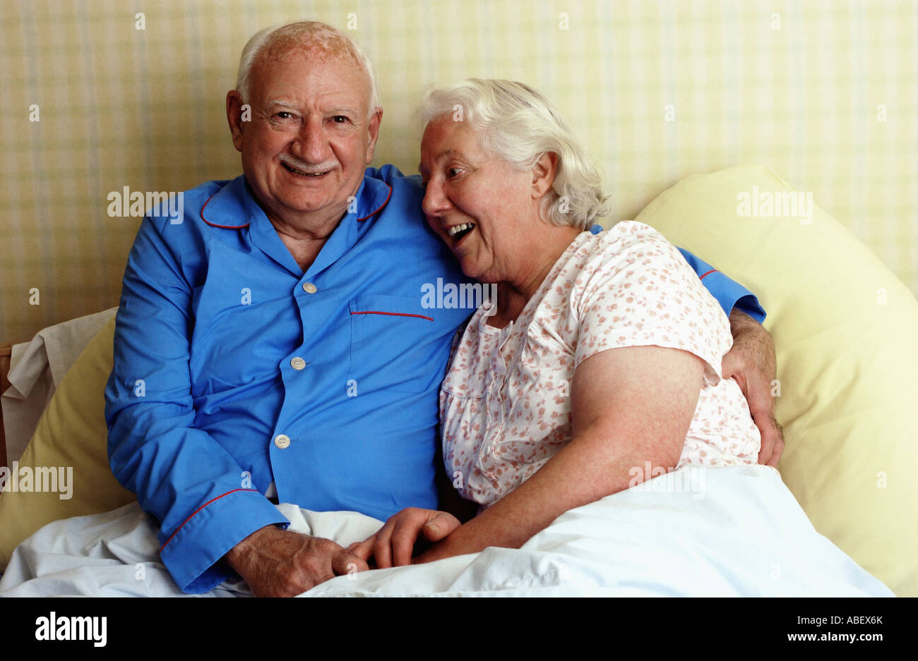 Senior couple smiling in bed - Stock Image