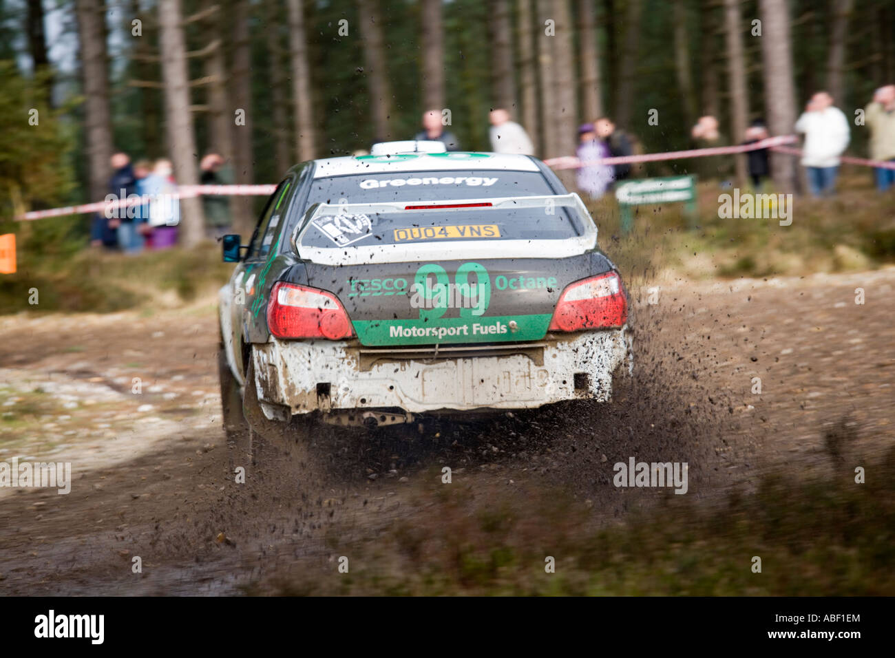 Green And White Subaru Impreza Rally Car 99 Driving Action Spraying Gravel Stones Dirt Mud As It Turns A Corner