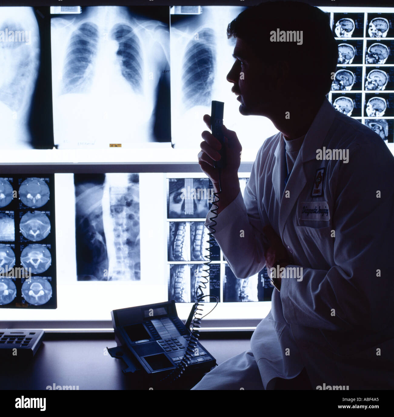 Medical - A doctor radiologist in a hospital X-ray analysis room reading X-rays of a chest and other parts of the body / USA. - Stock Image