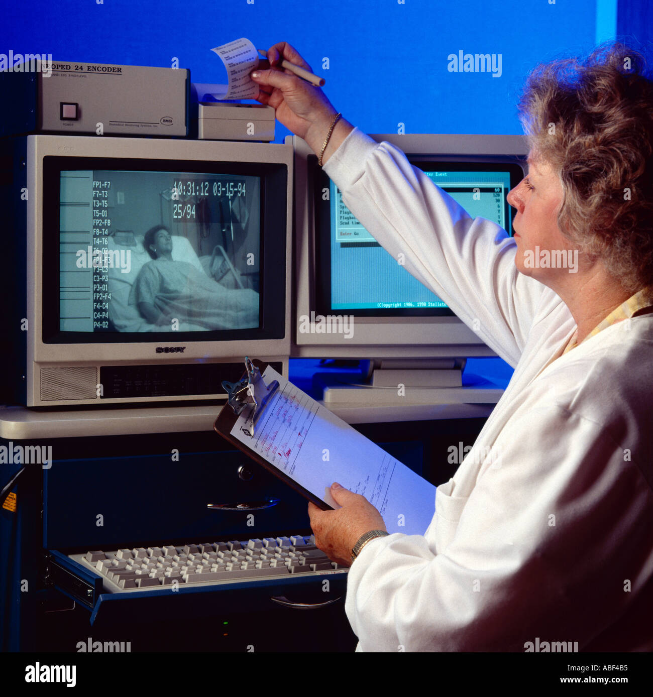 Sleep disorder research; A researcher uses a CRT monitor to remotely observe a woman during research into sleep disorders / USA. - Stock Image