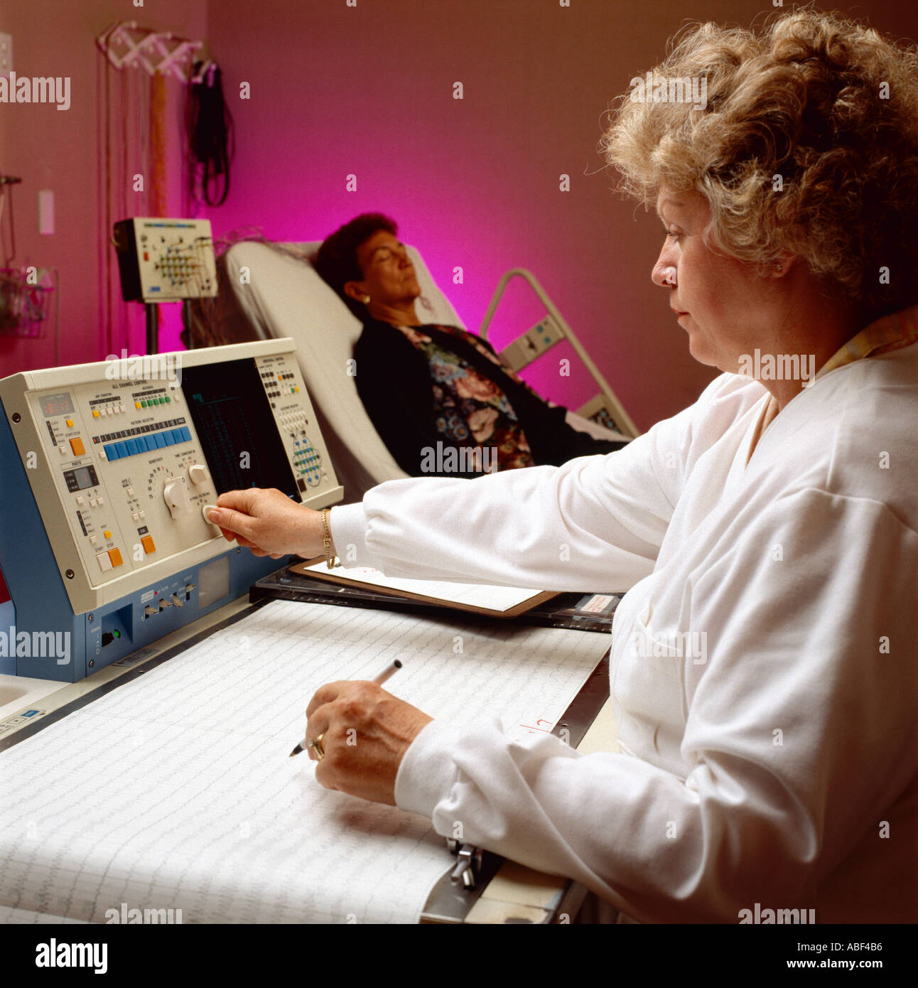 Sleep disorder research; A researcher monitors testing equipment while observing a woman during research into sleep disorders. - Stock Image