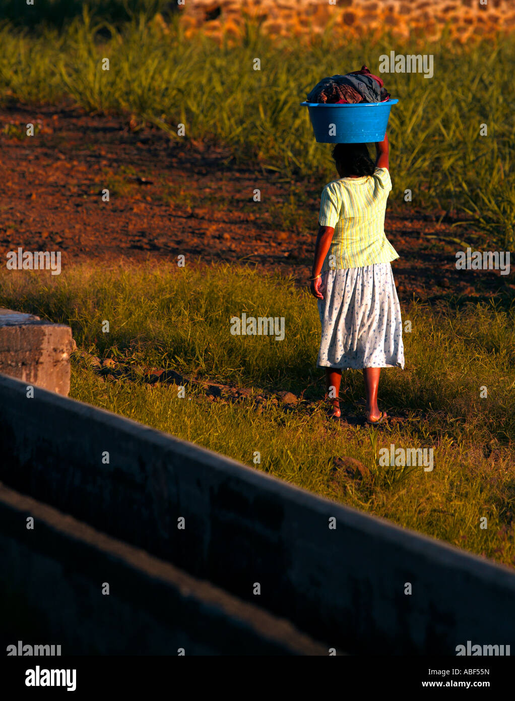 Lady returns home with the family's washing - Mauritius. Stock Photo