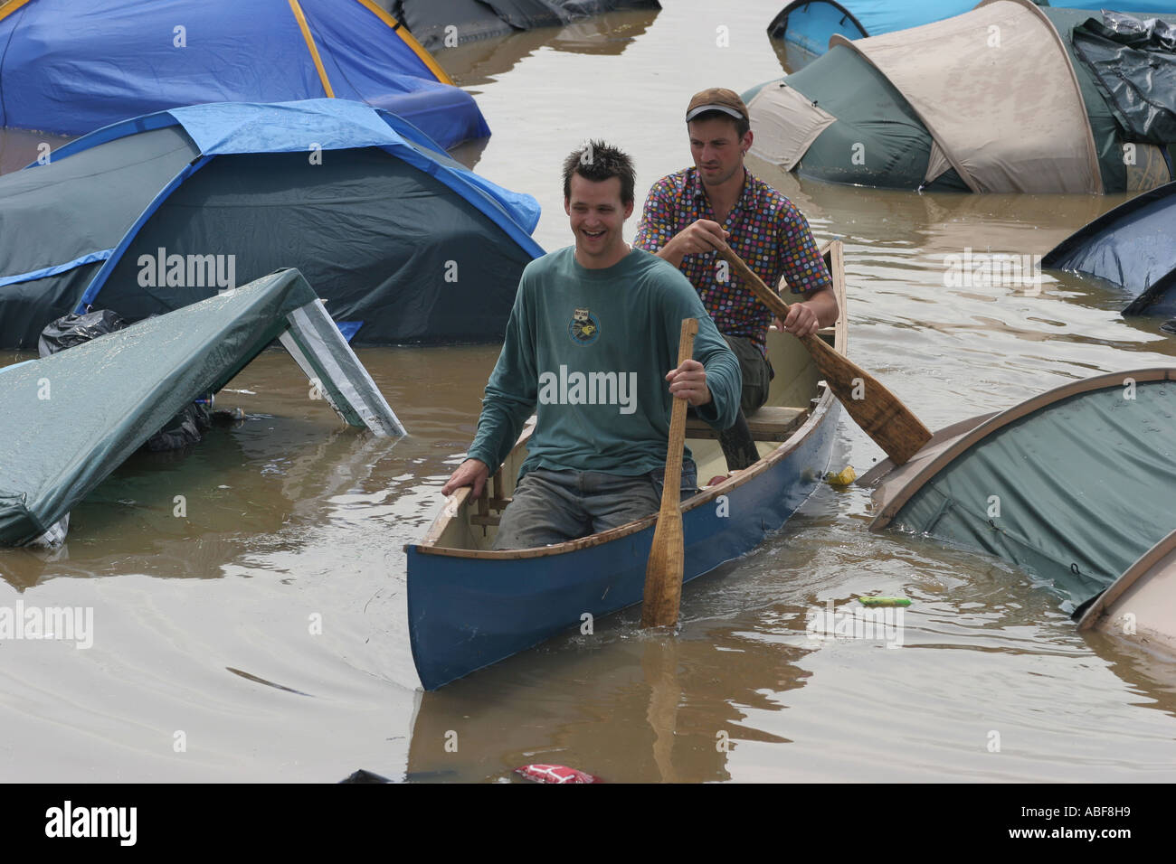 Two men canoeing around the flooded Pennard Hill campsite.   Glastonbury music festival 2005. Worthy Farm Somerset England. - Stock Image