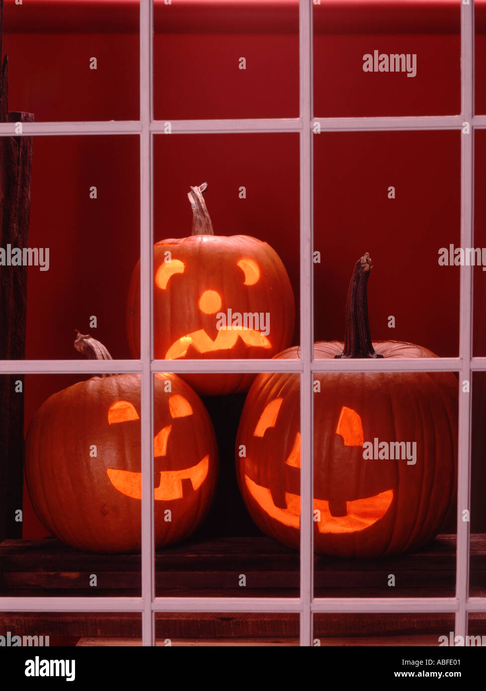 Three Jack O Lanterns peer out from behind a window frame while celebrating All Saints Day - Stock Image