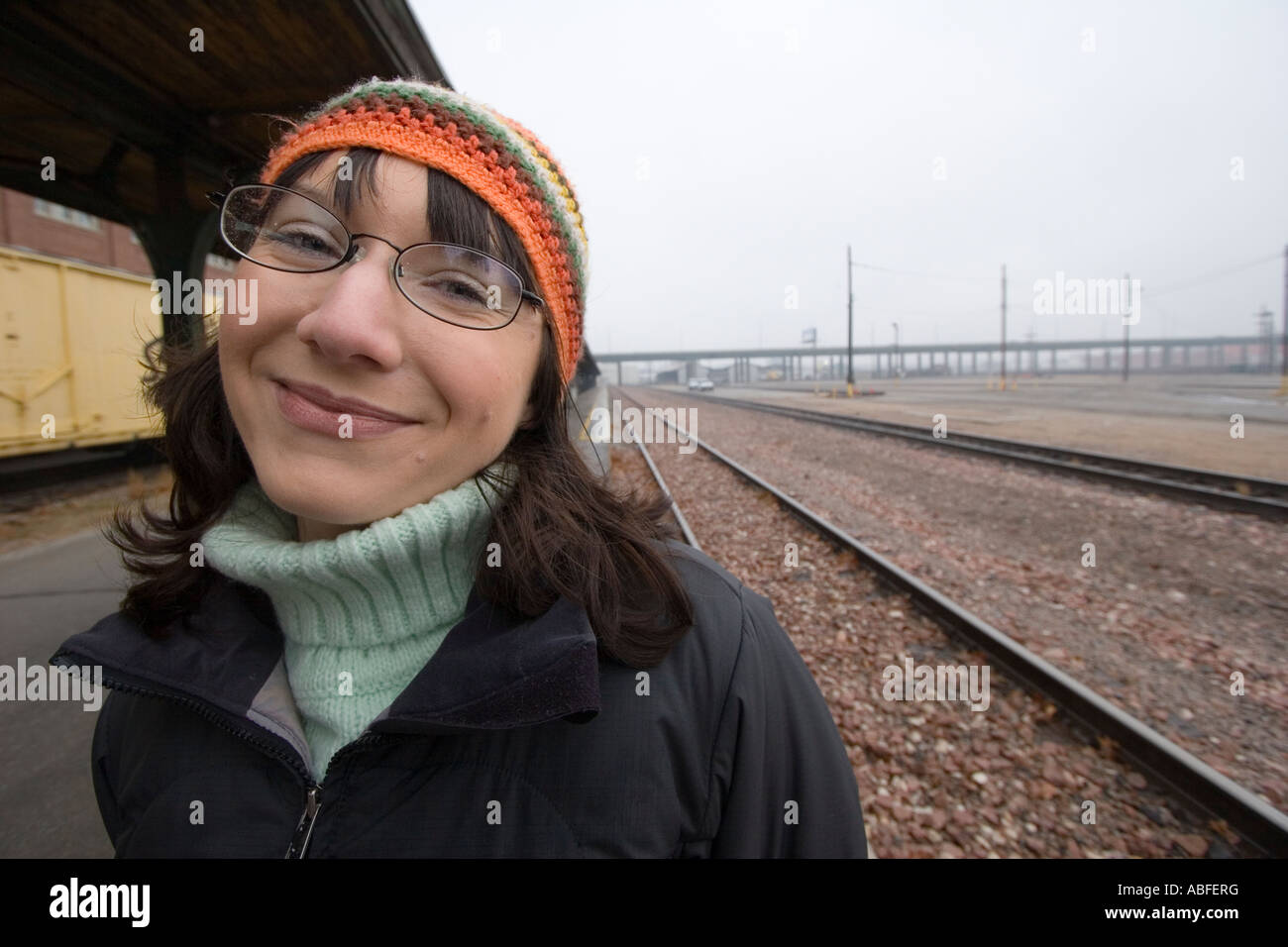 A woman standing at a railyard during the winter in Lincoln, Nebraska. - Stock Image