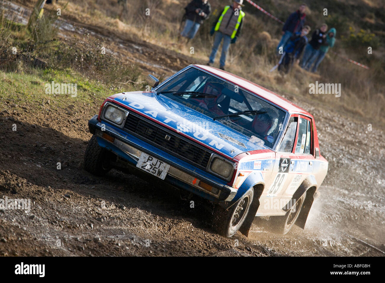 Muddy red white and blue Nissan Datsun Violet rally car driving on ...