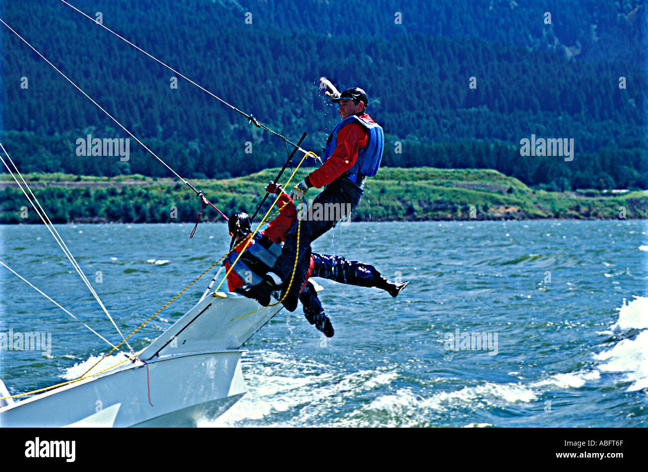 A 49er capsizes despite the crew s efforts to counterbalance it - Stock Image