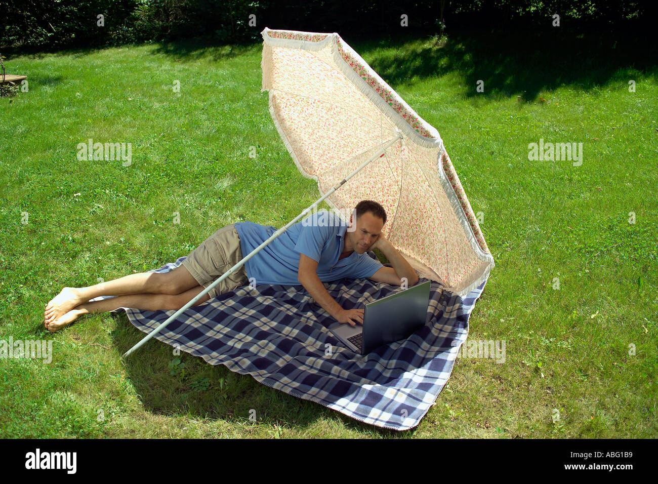 man with his laptop computer under a sunshade - Stock Image