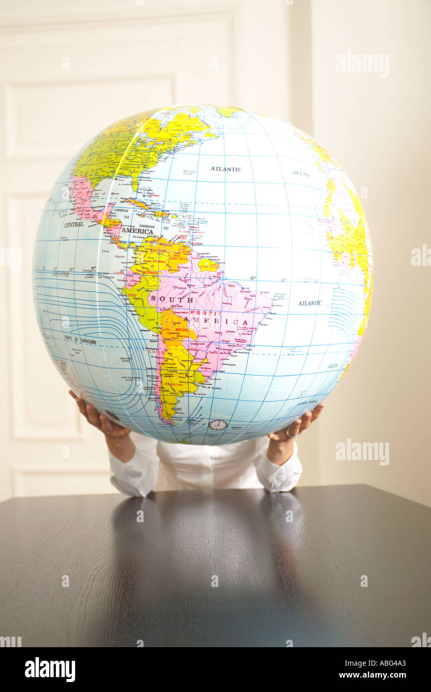 hands holding an inflatable globe Americas prominent - Stock Image