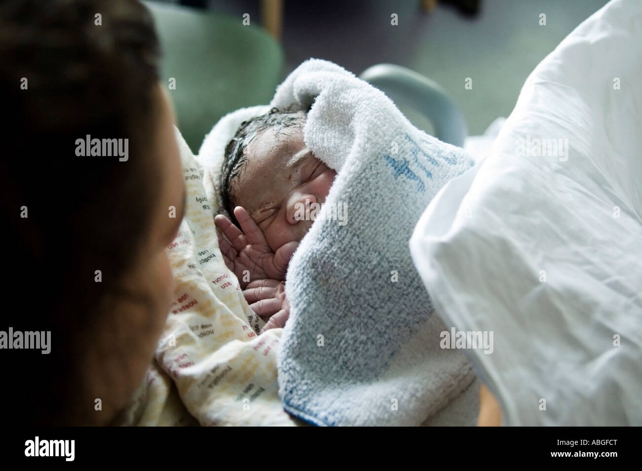 Newborn baby girl is just born at hospital. She is just 10 minutes old, wrapped in towel she is in her mum's arm. Stock Photo