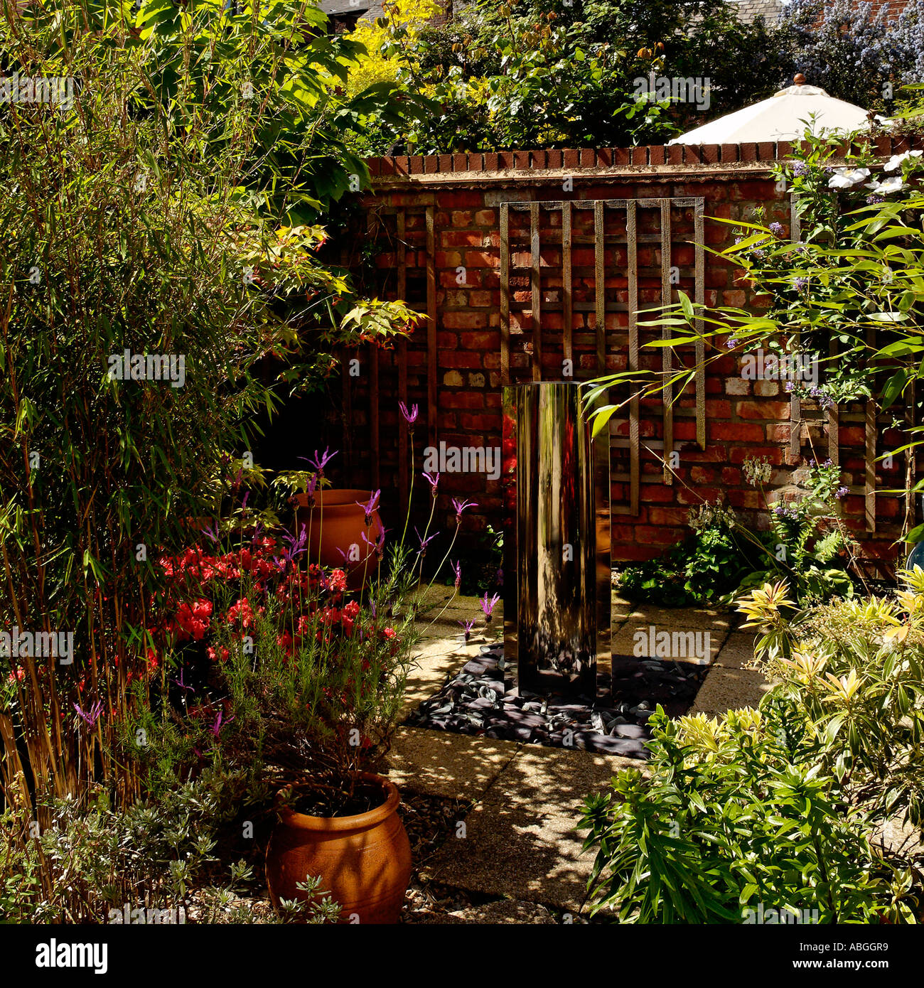 Dappled light in a contemporary patio garden - Stock Image