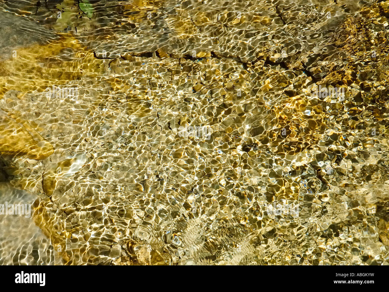 Rippling waves of a mountain brook generates light interferences in cristall clear water - Stock Image