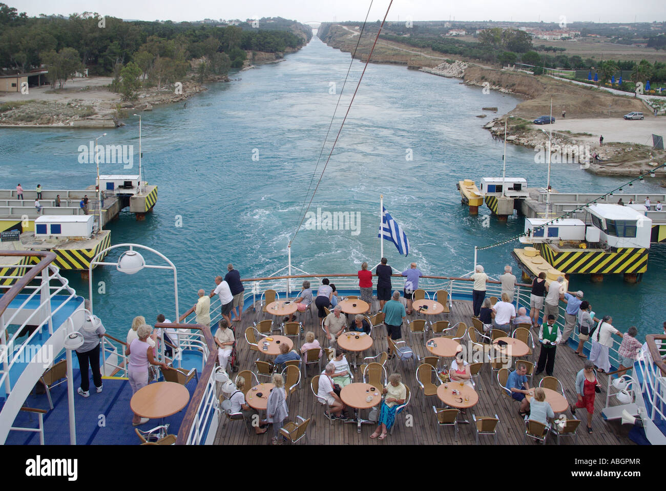 Passengers on stern leisure deck of Cruise ship passing over submersible road bridge across Corinth Canal connects Gulf of Corinth with Saronic Gulf Stock Photo