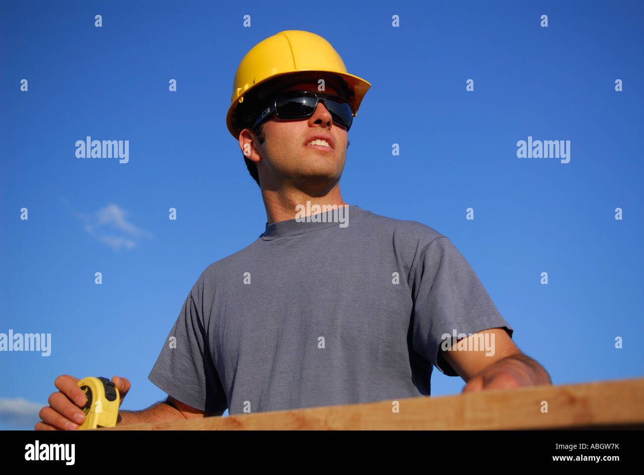 Construction worker carpenter in hard hat looking up while measuring plank of wood with tape measure against blue - Stock Image
