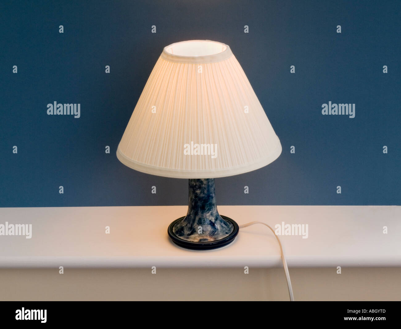 Table Lamp Lit Up With Cream Lamp Shade On White Windowsill With