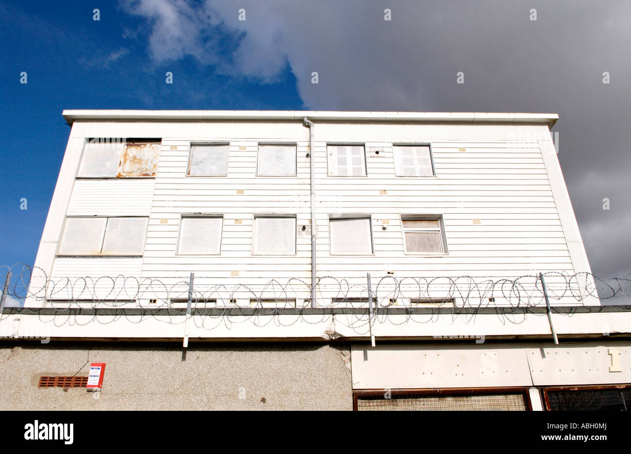 Derelict Block Of Flats Boarded Up On Run Down Shopping Centre With Running Wiring Under House Razor Wire Gurnos Estate Merthyr Tydfil South Wales Uk