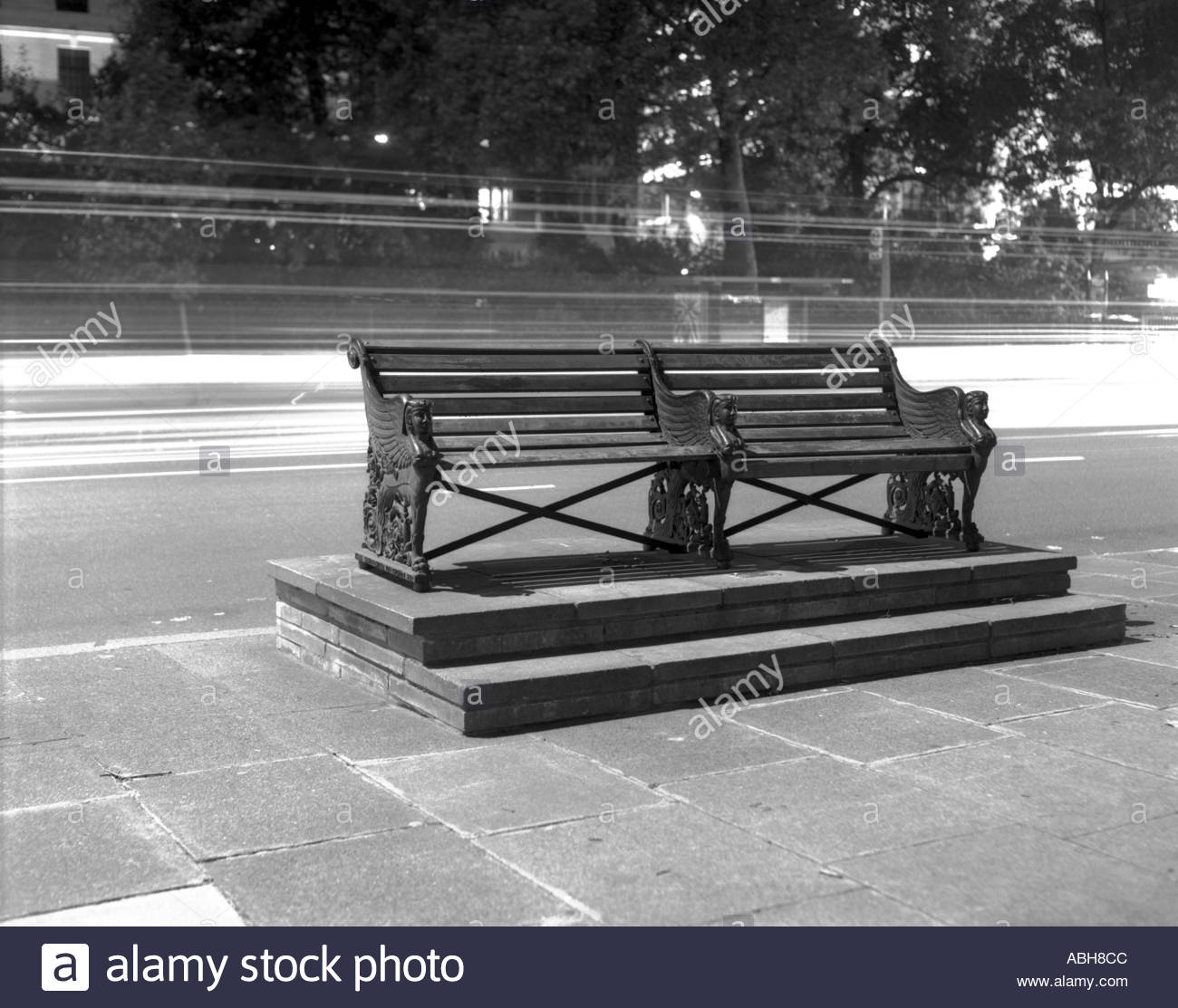 bench on the embankment westminster london in black and white with trails of car lights behind - Stock Image