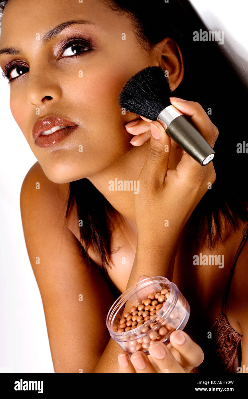 Portrait of a young woman applying make-up - Stock Image