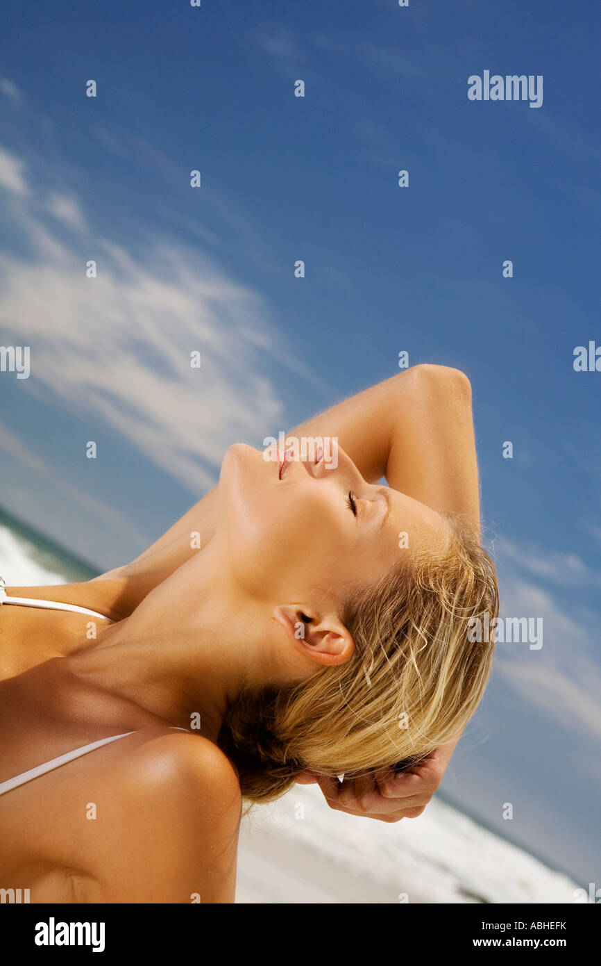 Young woman lying on beach, head back - Stock Image