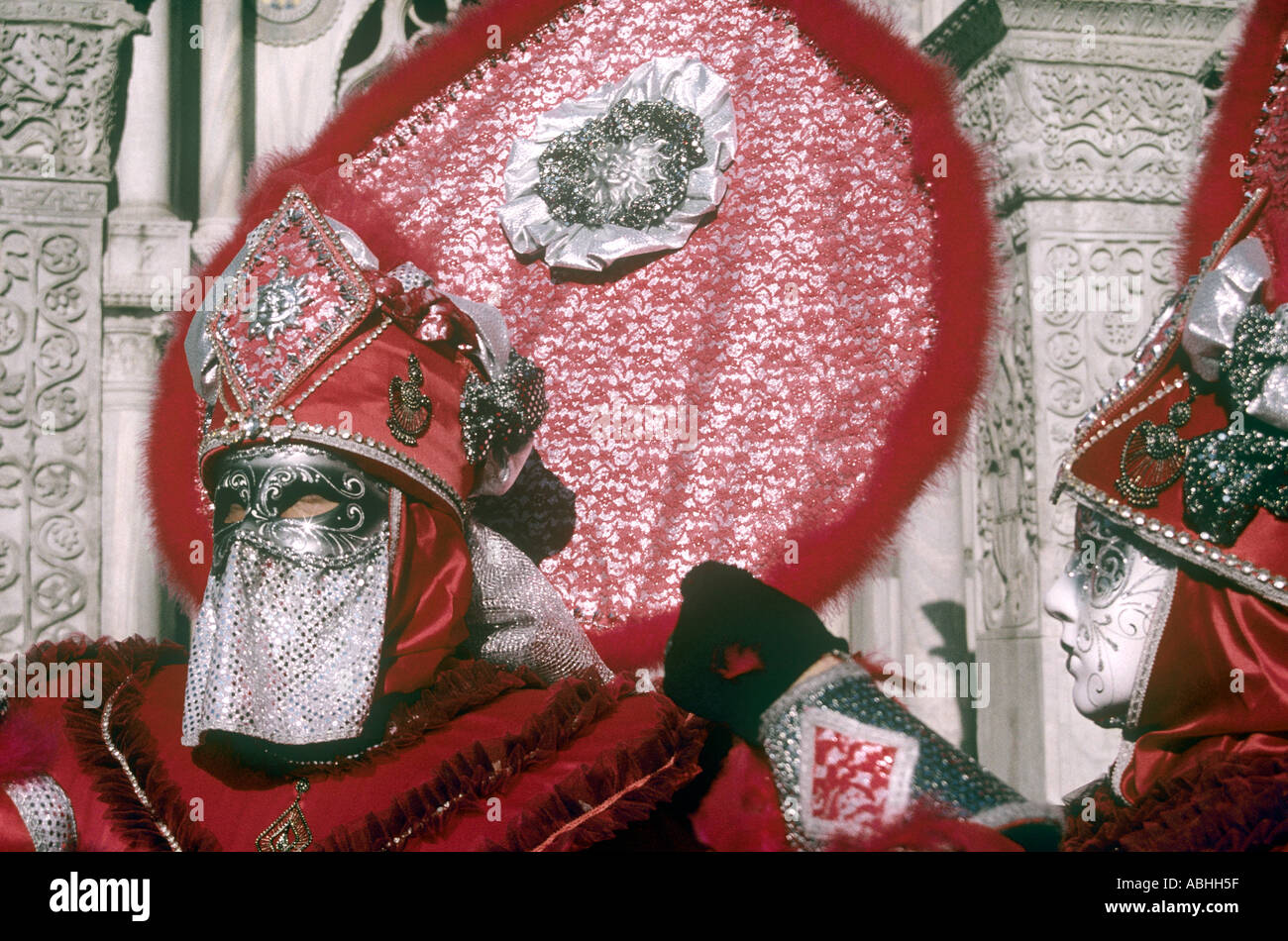 One red clad carnival goer in mask and outfit outside church in Venice Italy - Stock Image