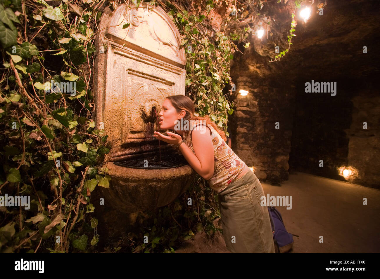 Woman tasting red wine of the wine fountain in Buda Castle Labyrinth Buda Budapest Hungary Stock Photo